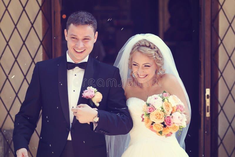 Marié et jeune mariée sortant de l'église images stock