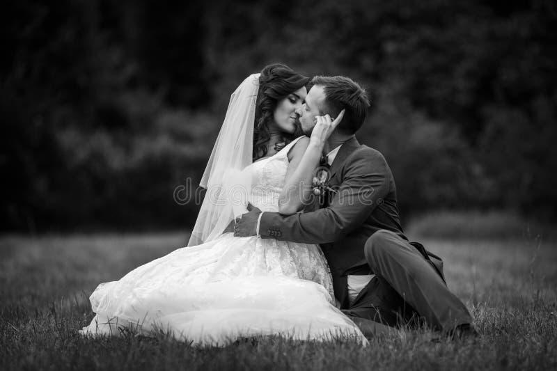 Marié heureux beau étreignant et embrassant la belle jeune mariée tandis que s photos stock