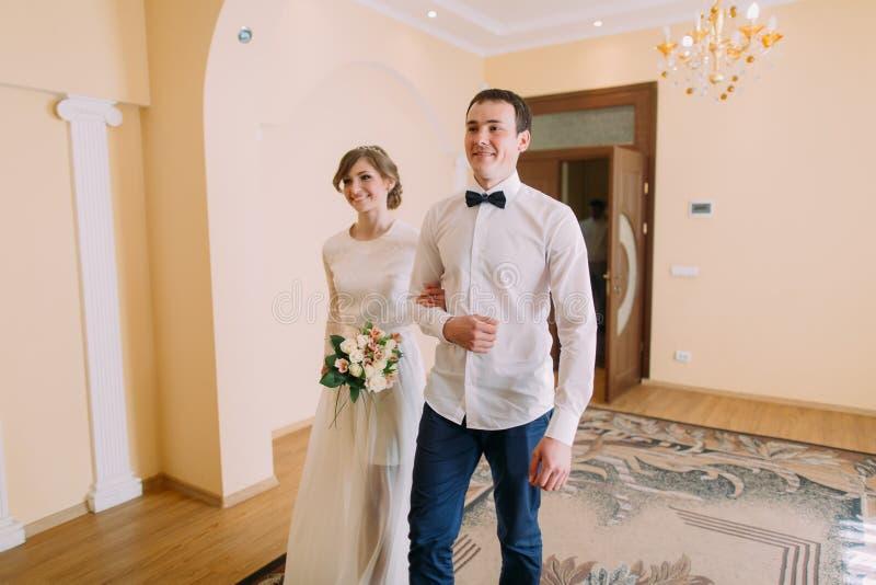 Marié heureux et jeune mariée marchant main dans la main au bureau d'enregistrement civil image libre de droits