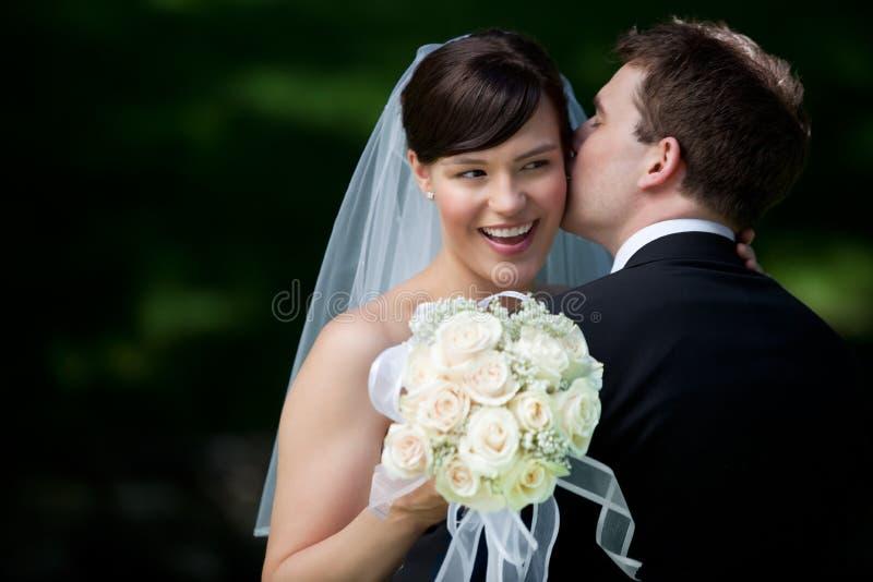 Marié Kissing Bride sur l'oreille photo libre de droits