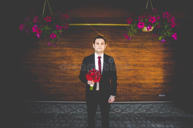 Marié magnifique élégant avec le lien rouge posant avec le bouquet rouge à t image libre de droits