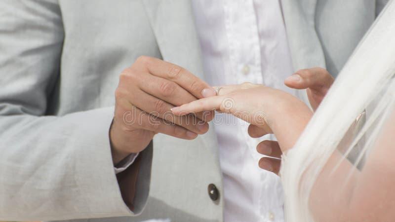 Marié mettant l'anneau de mariage sur bride' ; main de s photographie stock libre de droits