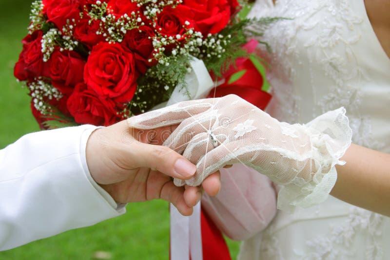 Marié retenant sa main gauche de mariée (juste mariée) photo libre de droits