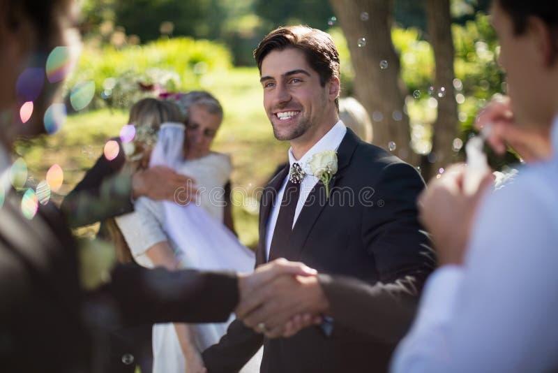 Marié serrant la main avec l'invité en parc image stock