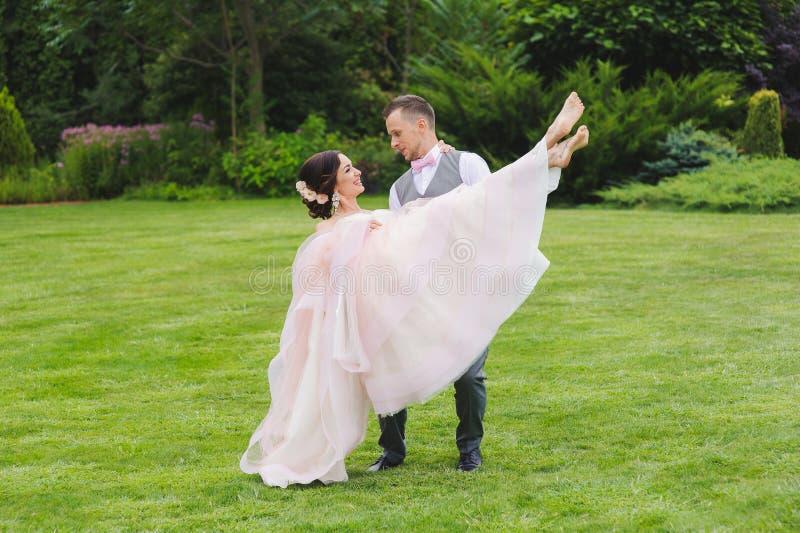 Marié tenant la belle jeune mariée dans des ses bras images libres de droits