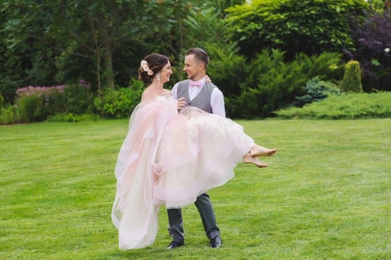 Marié tenant la belle jeune mariée dans des ses bras photos libres de droits