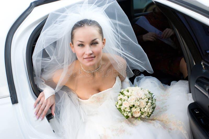 Mariée avec des fleurs dans le véhicule blanc photographie stock