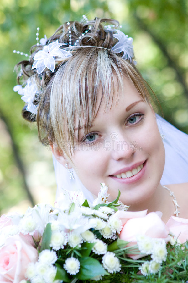 Mariée avec un bouquet de fleur par l'arbre photos stock