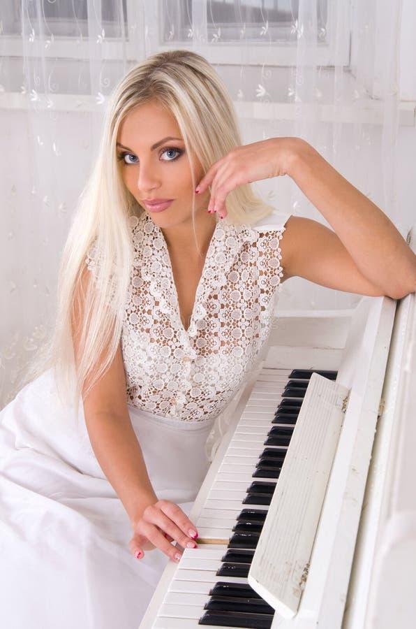 Mariée blonde près du piano image libre de droits