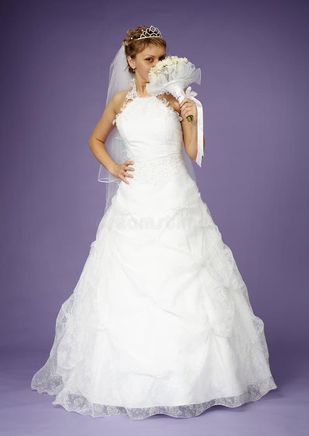 Mariée dans la robe blanche avec le bouquet photographie stock