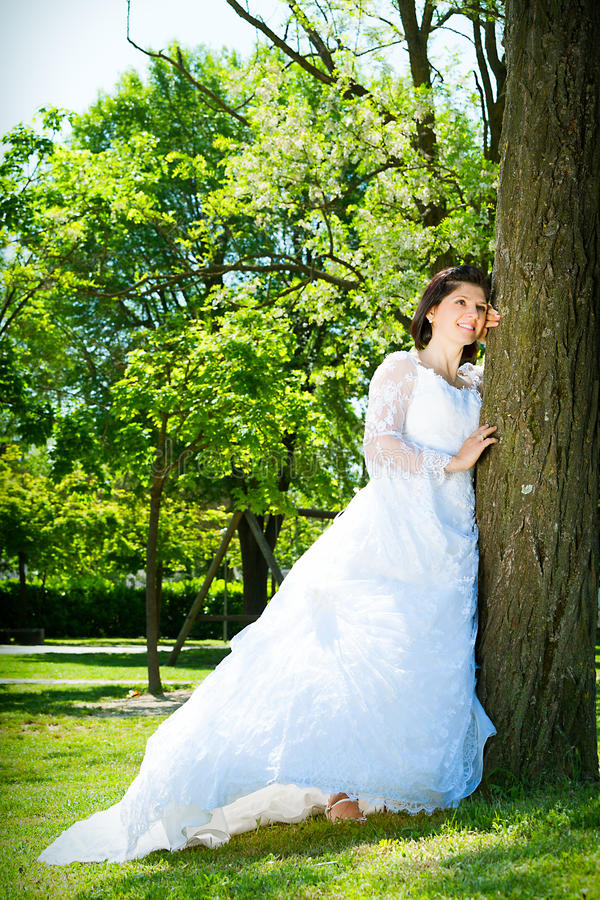 Mariée dans le blanc Au parc près d'un arbre photos libres de droits