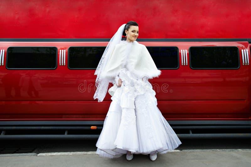Mariée de beauté sur le véhicule rouge de limousine de fond photo stock