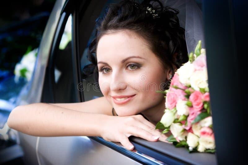 Mariée de sourire s'asseyant dans le véhicule photographie stock