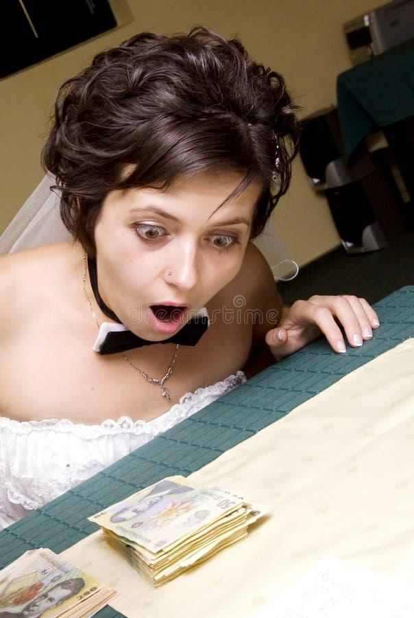 Mariée drôle regardant la pile du MOIS photographie stock