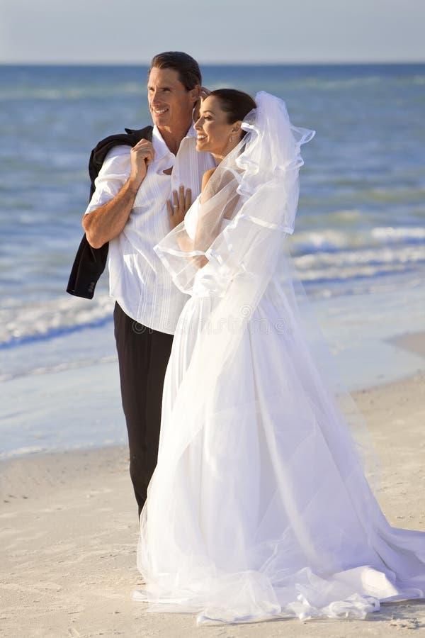 Mariée et ménages mariés par marié au mariage de plage photos libres de droits