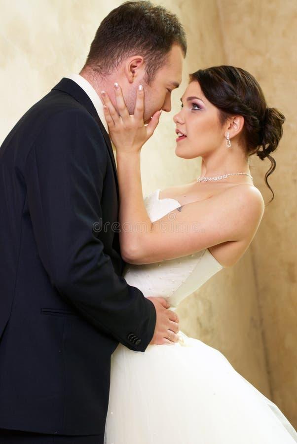 Mariée et marié étreignant dans la chambre vide image libre de droits