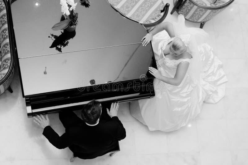 Mariée et marié au piano photographie stock libre de droits