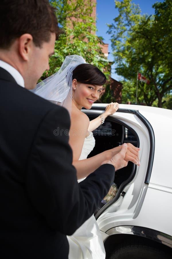 Mariée et marié avec la limousine image stock