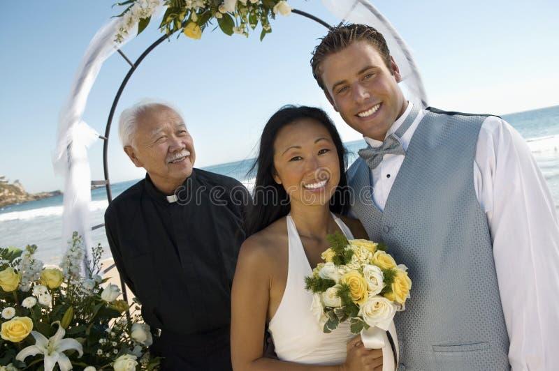 Mariée et marié avec le prêtre sous le passage arqué images libres de droits