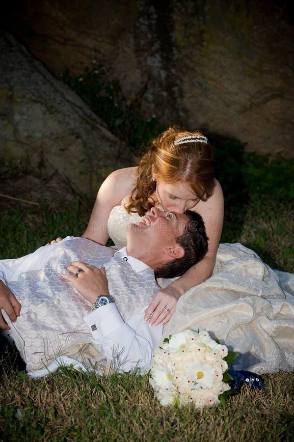 Mariée et marié embrassant et s'asseyant sur l'herbe verte image stock
