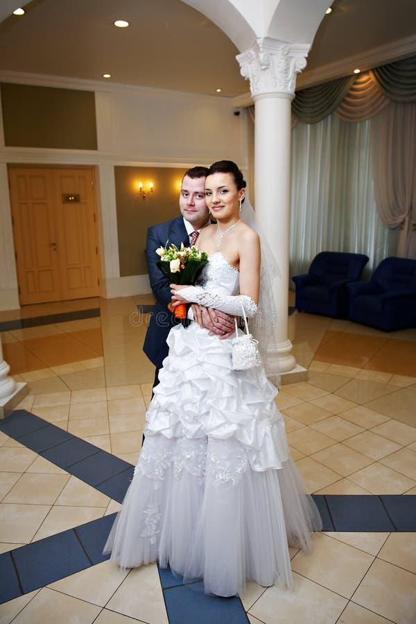 Mariée et marié heureux dans le palais de mariage photos stock