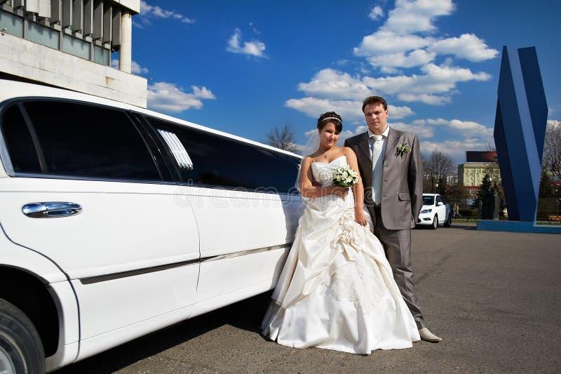 Mariée et marié heureux près de limousine de mariage photos stock