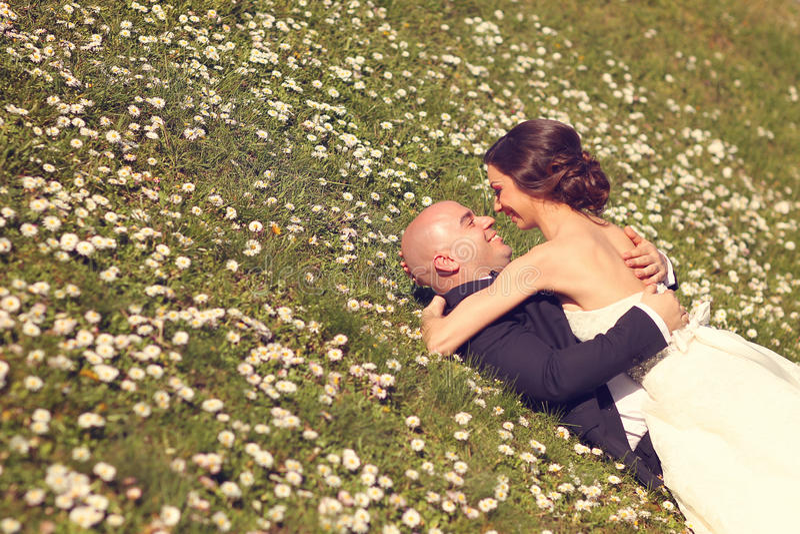 Mariée et marié se trouvant sur l'herbe photographie stock libre de droits