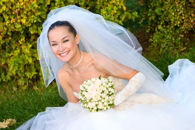 Mariée heureuse avec un bouquet de fleur dans des ses mains image stock