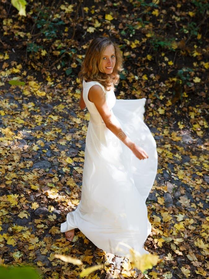 Mariée heureuse dans la robe blanche dans la défoliation d'automne photos libres de droits