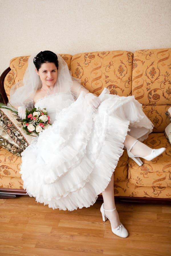 Mariée heureuse sur le sofa photos stock
