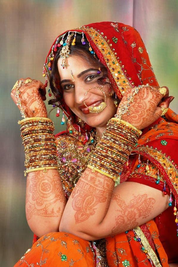 Mariée indienne dans sa robe de mariage affichant des bracelets images stock