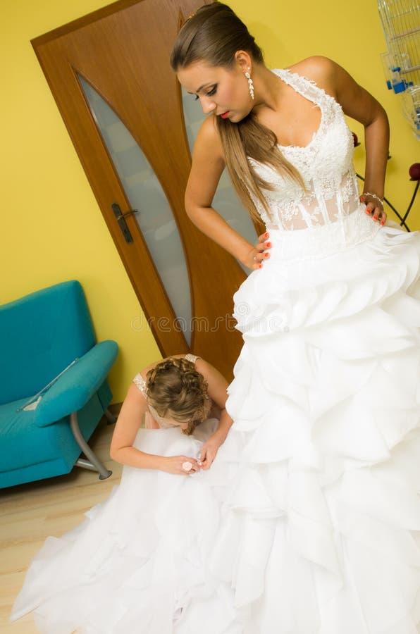 Mariée mettant sur la robe de mariage photo stock