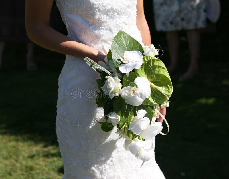 Mariée retenant un bouquet des fleurs images stock
