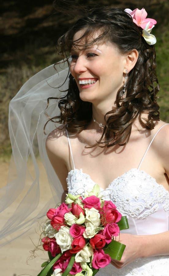 Mariée riant avec le voile et le bouquet photographie stock