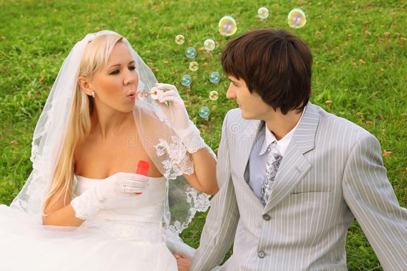 Mariée s'asseyant avec le marié et les bulles de soufflement image libre de droits