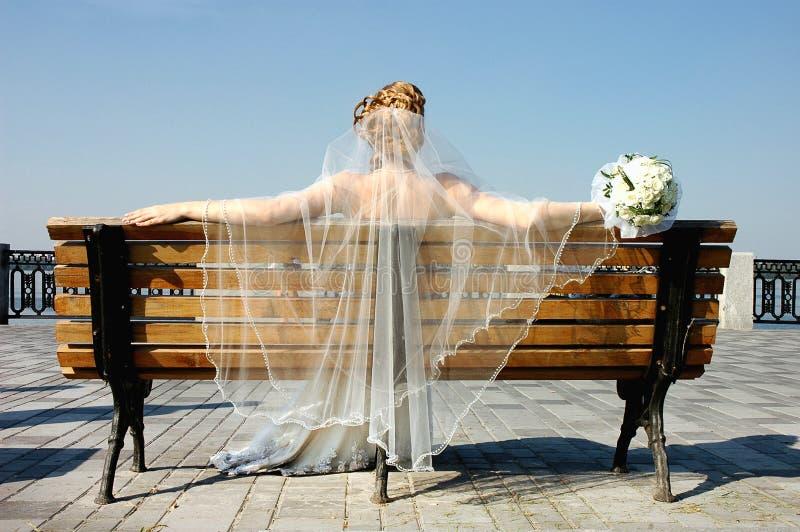 Mariée sur un banc image stock