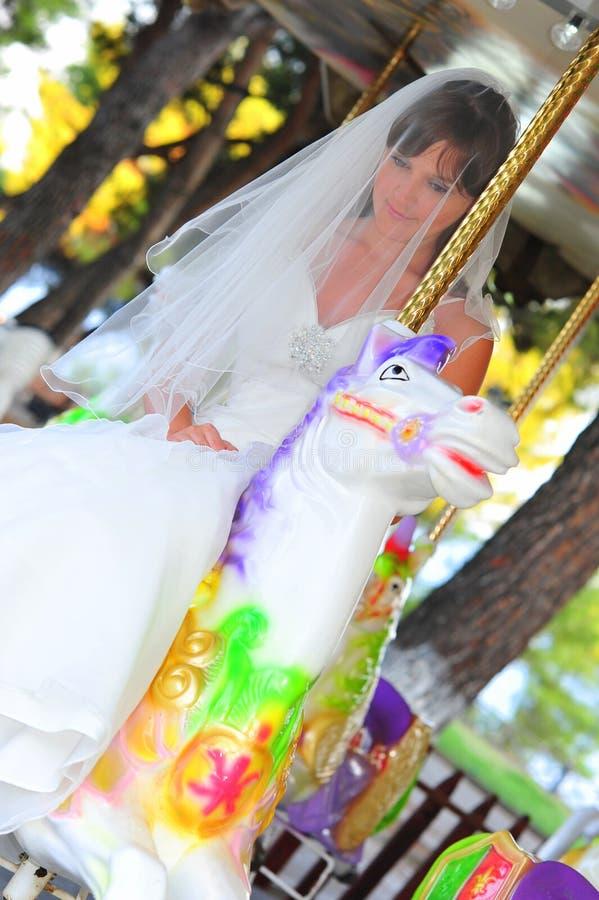 Mariée sur un cheval blanc de carrousel image libre de droits