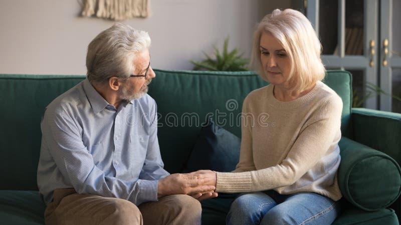 Mari âgé moyen tenant des mains, épouse bouleversée de caresse à la maison photo stock
