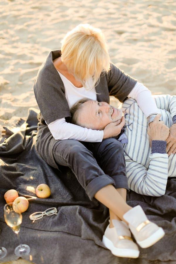Mari caucasien supérieur se trouvant sur les genoux et le plaid d'épouse, le champagne et les fruits sur la plage de sable images libres de droits