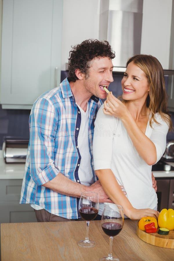 Mari de alimentation de sourire de belle épouse dans la cuisine photo libre de droits