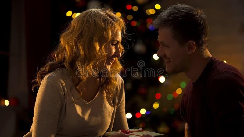 Mari de soin donnant son cadeau de Noël d'épouse, surprise agréable, tradition de vacances photos libres de droits