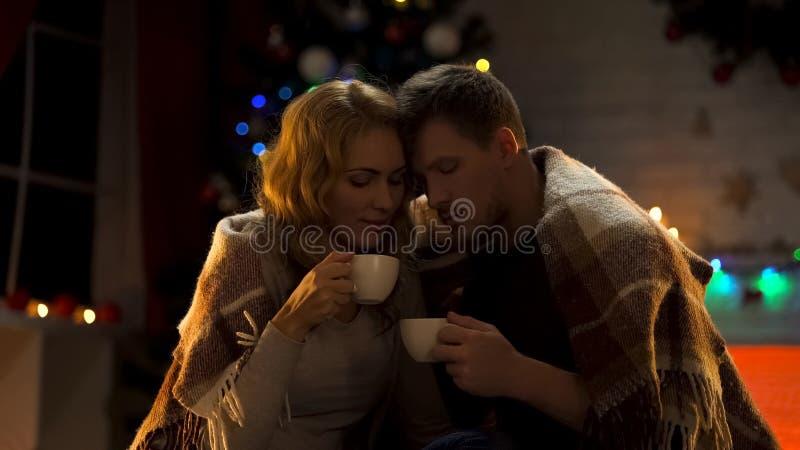 Mari doux et épouse buvant du cacao chaud sous le plaid confortable, roman à Noël images libres de droits