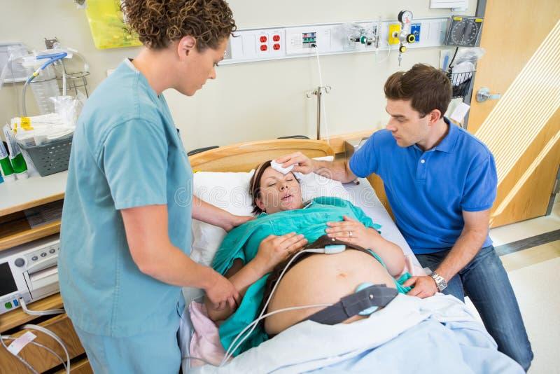 Mari essuyant le front de l'épouse enceinte photographie stock libre de droits