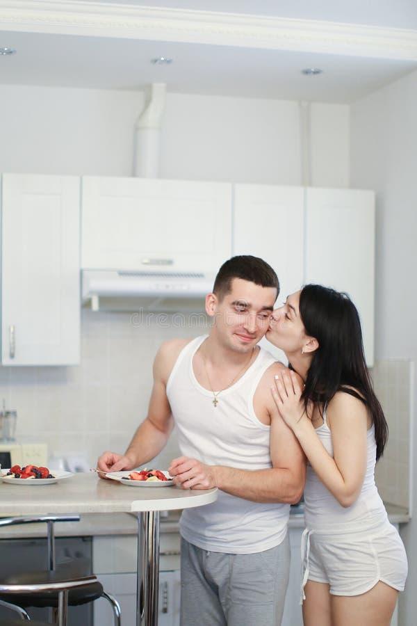 Mari et épouse faisant cuire le breakfat dans le matin sur la cuisine, chemises de port images stock