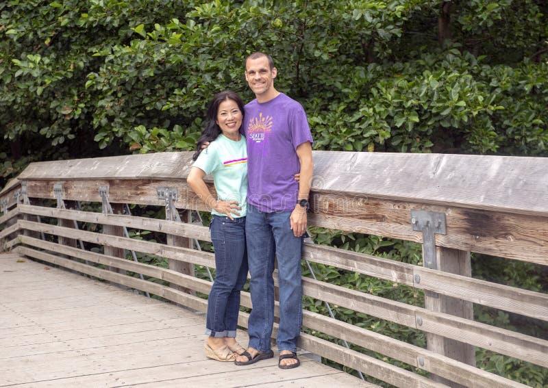 Mari et épouse posant sur un pont en bois en Washington Park Arboretum, Seattle, Washington photo libre de droits