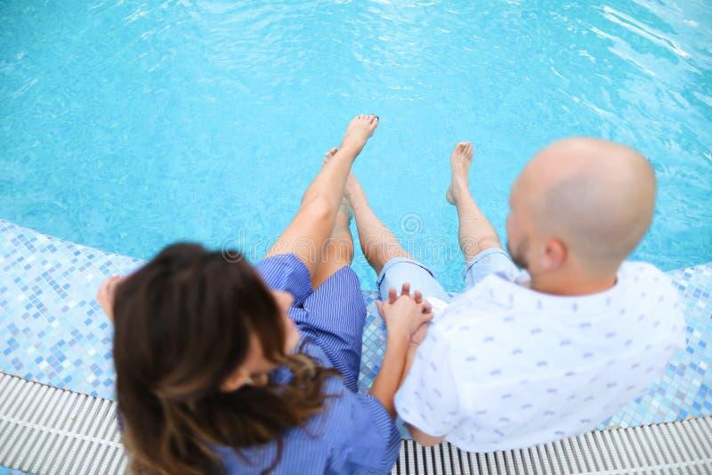 Mari et épouse reposant la piscine proche aux pieds nus image stock