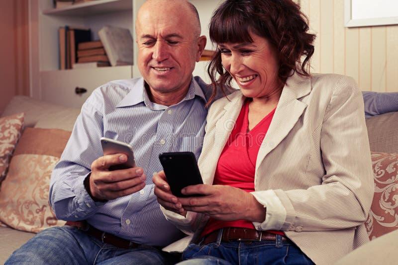 Mari et épouse souriant et regardant des téléphones images stock
