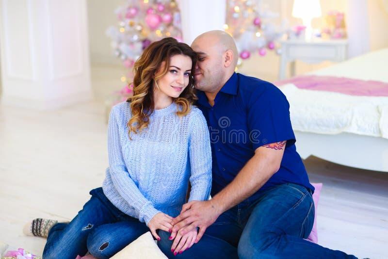 Mari heureux étreignant l'épouse et s'asseyant près de l'arbre de Noël décoré images libres de droits