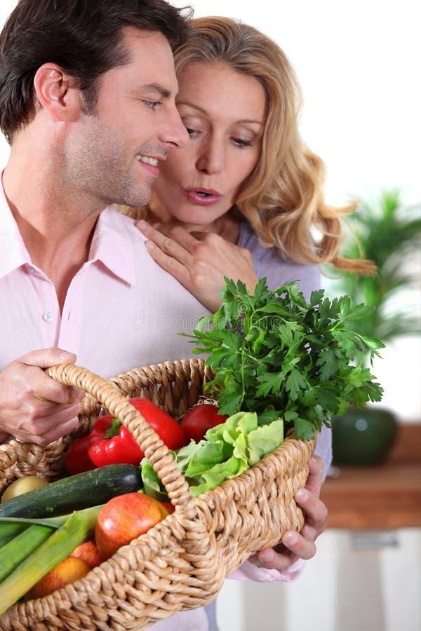 Mari montrant des légumes d'épouse images stock
