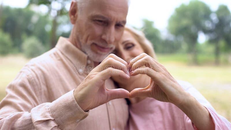 Mari romantique et épouse montrant le geste de coeur à la main, tendresse de vieillesse photos libres de droits